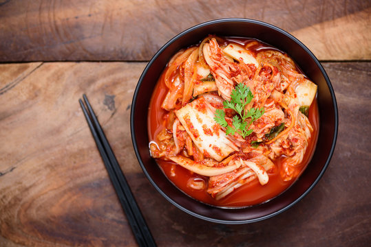 Kimchi cabbage in a bowl with chopsticks on wooden background, Korean food, top view