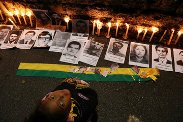 A girl is seen next to placards with pictures of missing people and victims of the military dictatorship during a protest against Brazilian President Jair Bolsonaro, in front of a former DOI-CODI torture unit in the 1970's in Sao Paulo