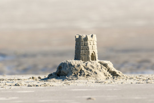 Detailed sand castle on the beach with a tidal pool in the background