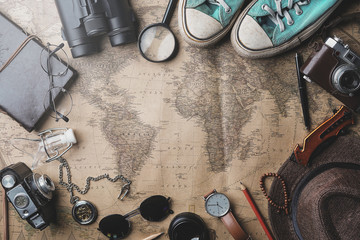 Poster Retro Travel Concept Background. Overhead View of Traveler's Accessories on Old Vintage Map