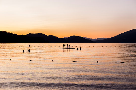 Silhouettes of people standing on a dock in a lake at sunset