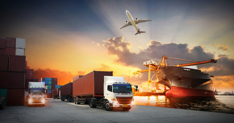 Container truck in ship port for business Logistics and transportation of Container Cargo ship and Cargo plane with working crane bridge in shipyard at sunrise, logistic import export and transport  Wall mural