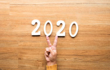 2020 new year celebration concepts with text number and human hand showing V sign on wood background