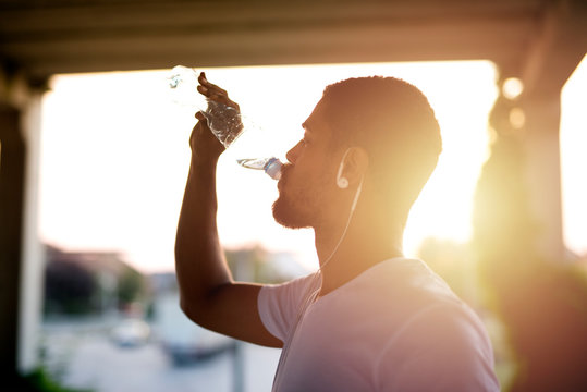 Attractive athlete sportsman drinking water after training and hydrating his body.