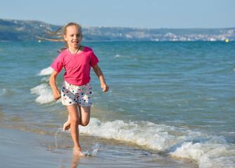 Happy child girl on sea beach having fun.