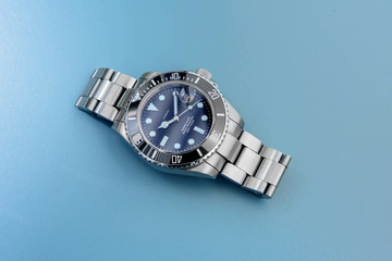 Big stainless steel sport divers watch on light blue background