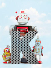 Wall Mural - retro robots holding a big  metal letter K with blue sky