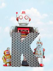 Fototapete - retro robots holding a big  metal letter K with blue sky