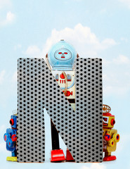 Fototapete - retro robots holding a big  metal letter  N with blue sky
