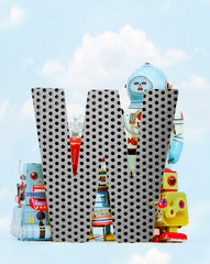 Fototapete - retro robots holding a big  metal letter W with blue sky
