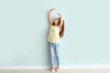 Cute little girl measuring her height near wall