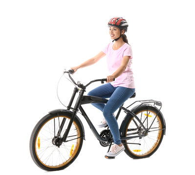 Beautiful young woman riding bicycle against white background