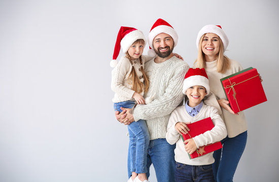 Happy family with Christmas gifts on light background