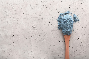 Blue tea matcha in a spoon on concrete surface with copy space
