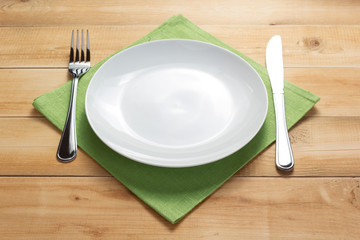 plate, knife and fork at rustic wooden background