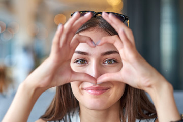 Beautiful woman looking through heart gesture made with hands