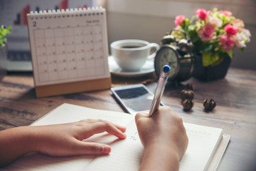 On book or diary,Man's hand planner or organizer writing daily appointment,mark and noted schedule(meeting) on book or diary at office desk.Planner concept
