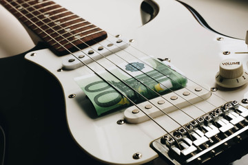 Money under the strings of a guitar. One hundred euros under the strings of a guitar.