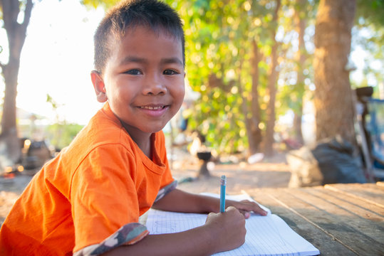 Asian child (poor kid) study at old home. Asia boy learning to drawing, painting with color pencil. Poverty child, smile, lying on dirty wooden table and writing book. Poor Quality Education Concept.