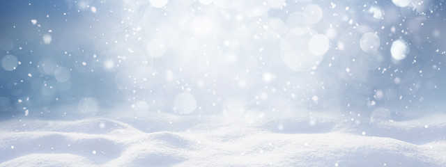 Photo sur Plexiglas Campagne Winter snow background with snowdrifts, with beautiful light and snow flakes on the blue sky, beautiful bokeh circles, banner format, copy space.