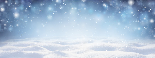 Winter snow background with snowdrifts, with beautiful light and snow flakes on the blue sky in the evening, banner format, copy space.