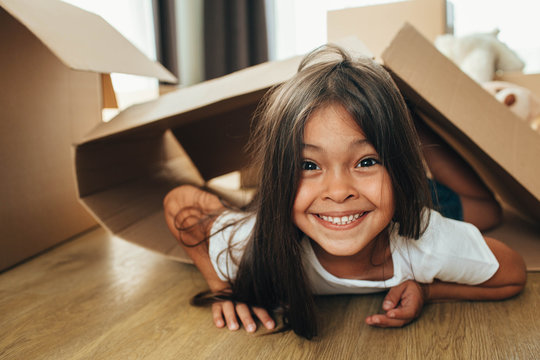 Happy mixed race little girl playing with cardboard boxes, having fun while moving home