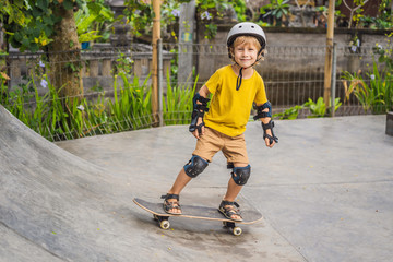 Athletic boy in helmet and knee pads learns to skateboard with in a skate park. Children education, sports