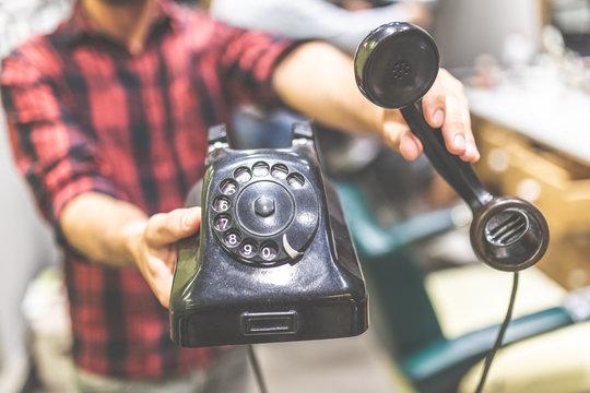 Close up of fashionable man hands holding vintage landline telephone.