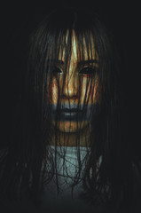 Scary witch with black eyes on dark background