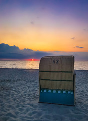 Traditional Baltic beach chair at the German Baltic Sea coast in the sunset