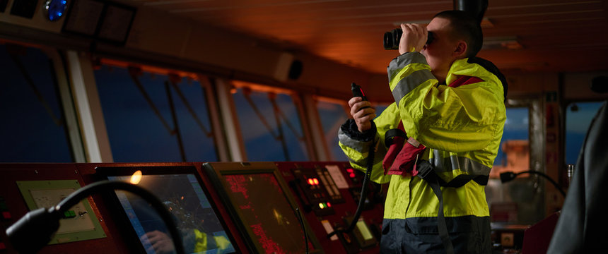Navigator. pilot, captain as pat of ship crew performing daily duties with VHF radio, binoculars on board of modern ship with high quality navigation equipment on the bridge on sunrise.