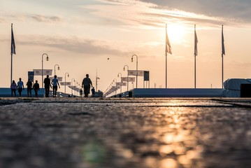 people walking on the Sopot pier during a charming sunrise