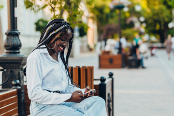 Portrait of a smiling young African American girl with pigtails with a phone sitting on a bench on...