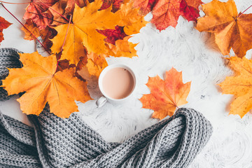 Fototapete - Autumn home cozy composition a cup of coffee with maple leaves.Top view