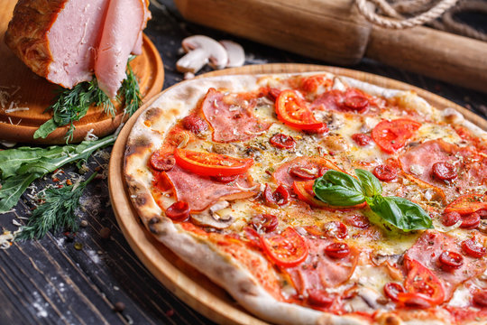 Aromatic pizza with sausage and tomatoes is decorated with basil