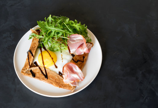 Galette bretonne  with fried eggs, arugula and bacon on a black background.