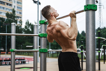 Muscular man doing pull-ups on horizontal bar
