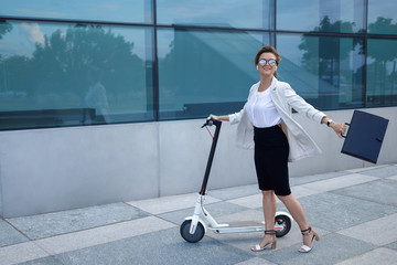 Young and beautiful businesswoman rides electric scooter