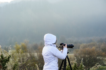 photographer with camera and tripod outdoor taking landscape picture