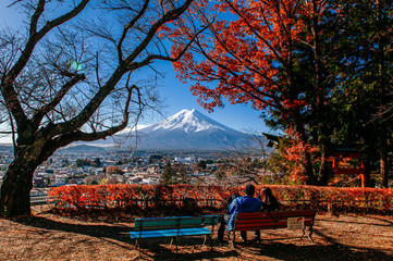 Mount Fuji and red maple tree with sweet couple at Chureito Pagoda Arakurayama Sengen Park - Fujiyoshida