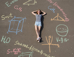 schoolgirl laying on a asphalt with chalk drawn mathenatics formulas and geometric figures