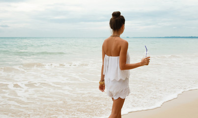 Beautiful woman wearing white jumpsuit walk on the beach