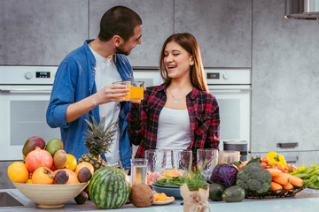 Portrait of happy young couple in kitchen cooking together drinking orange juice in the morning at home
