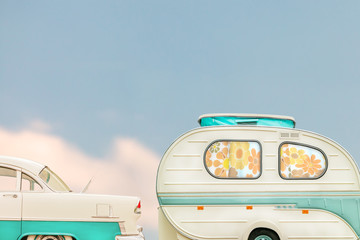 Retro classic car and seventies caravan with flower curtains