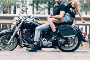 cropped view of young couple of bikers on black motorcycle on road