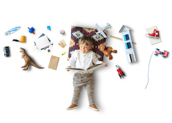 Fotomurales - Little boy lies and reads a book among his toys