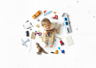Little boy sits and plays on the floor among his toys