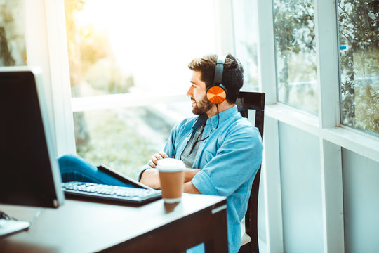 Happy Relaxed man drink coffee and Listen to music on headphones. working from home concept