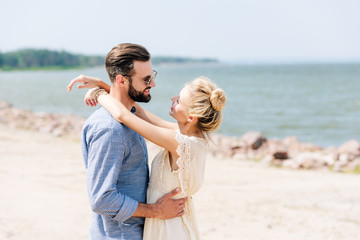happy blonde woman hugging smiling bearded boyfriend at beach