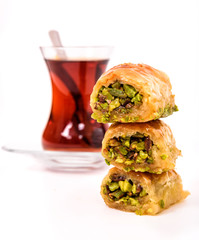 Traditional Turkish Dessert, Baklava on the wooden plate with pistachio nuts and Turkish Tea with spoon on the white surface.